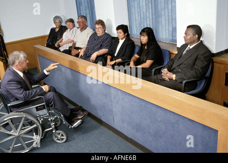 Lawyer Attorney in court in wheel chair addresses a mix race jury - Stock Photo