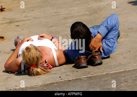 young couple laying lying on a slipwy beach fully clothed sunbathing in the summertime at cowes on the isle of wight - Stock Photo