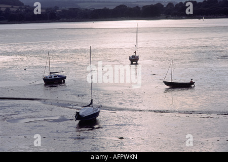 Four Small Boats on the Mud at Low Tide on the Exe Estuary near Sunset at Lympstone Devon - Stock Photo