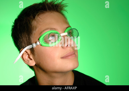 Portrait of a boy wearing green swimming goggles - Stock Photo