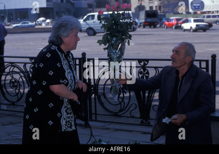 Elderly Georgian woman buying flowers from a street vendor in Dowbtown Tbilisi Georgia in the former USSR - Stock Photo