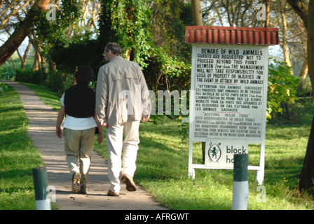 Couple walking past sign warning of the danger of wild animals in the grounds of Lake Naivasha Club Kenya East Africa - Stock Photo