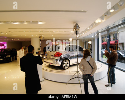 Young people taking pictures and admiring a completely chromed Toyota Auris car in the Toyota flagship showroom - Stock Photo