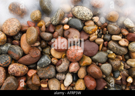 A crashing wave moves over colorful Great Lakes beach rocks on Lake Superior, Michigan - Stock Photo