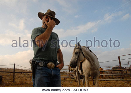 An Israeli cattle herder wearing a pistol in a farmyard in the Golan heights northern Israel - Stock Photo