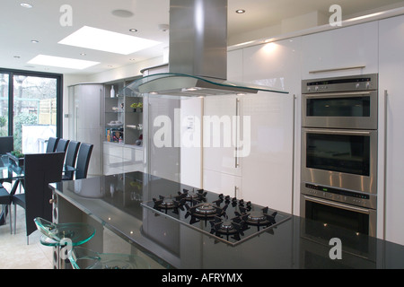 Extractor fan above hob in blue island unit in modern white kitchen stock photo royalty free - Kitchen island extractor fans ...