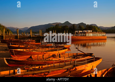View over rowing boats & cruiser on Lake Derwentwater towards Cat Bells in late evening light - Stock Photo