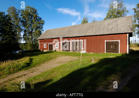Old Swedish barn in typical red color in the morning sun, Sweden - Stock Photo