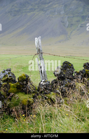 fence post and lava wall near Búðir Snaefellsnes Iceland - Stock Photo