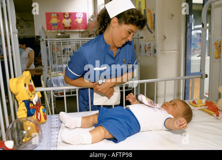 Staff nurse in childrens ward at Manchester NHS hospital. UK England   Nurse with baby in cot. HOMER SYKES - Stock Photo