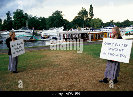 YOUNG WOMEN HOLDING QUIET PLEASE CONCERT IN PROGRESS SIGNS HENLEY FESTIVAL JUNE JULY HENLEY ON THAMES - Stock Photo