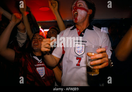 English football watching their favorite team on multi screens television room in a Sports bar London - Stock Photo