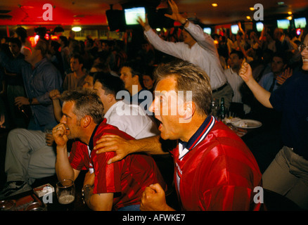 English football watching their favorite team on multi screens television room in a Sports bar London HOMER SYKES - Stock Photo