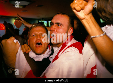 English football watching their favorite team England  on multi screens television room in a Sports bar London. - Stock Photo