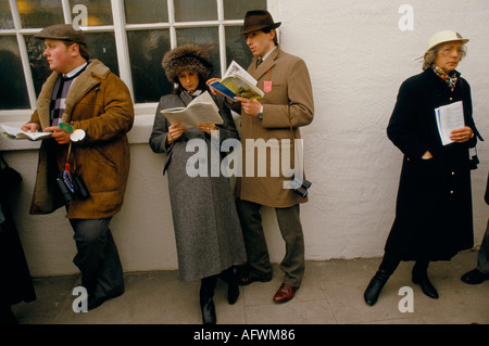 MAN WOMAN STUDYING HORSE RACING CARD AT THE GRAND NATIONAL AINTREE LIVERPOOL HOMER SYKES - Stock Photo