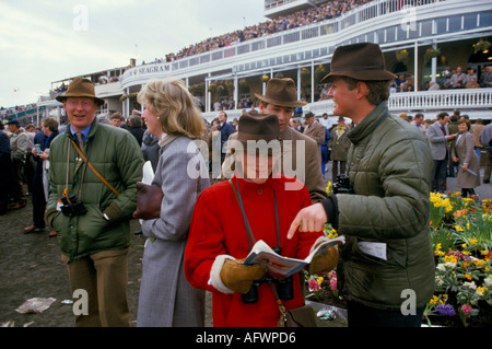PEOPLE IN GREEN WAXED PUFFA JACKETS AND FELT HATS STAND IN THE GROUNDS AT THE THE GRAND NATIONAL AINTREE LANCASHIRE - Stock Photo