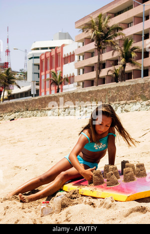 young mexican girl on a summer beach trip crouched playing in sand by Pacific ocean shoreline sandcastles on boogey - Stock Photo