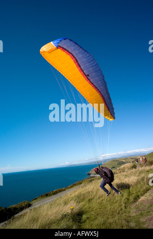 man with para glider taking off on Constitution hill Aberystwyth overlooking cardigan bay on a cloudless blue sky - Stock Photo