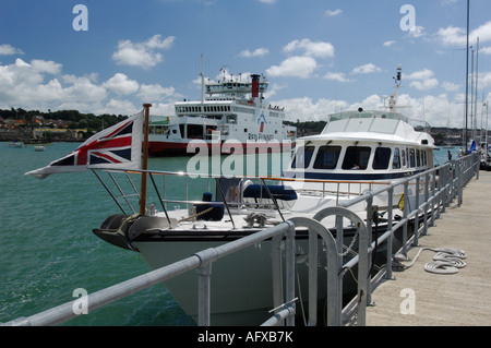 a large motor yacht cruiser at the mouth of the river medina at cowes yacht haven on the isle of wight in the solent - Stock Photo