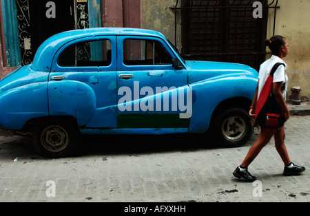 Cuba Havana Habana Vieja schoolboy passing a vintage oldtimer car - Stock Photo