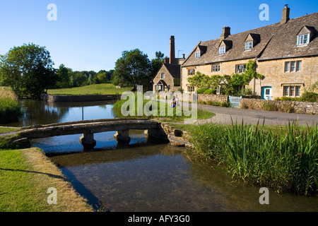 Ancient english village traditional cottages in summer sunshine pedestrian footbridge over the River Windrush Lower - Stock Photo