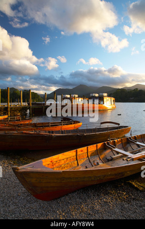 England, Cumbria, Lake District National Park. Wooden rowing boats and Derwent Water cruise ship moored at Jetty - Stock Photo