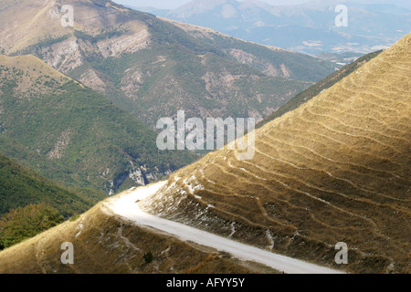 access road 'strada bianca' curves around the  Sasso Tetto  mountain at Pintura  in the Sibillini National Park - Stock Photo