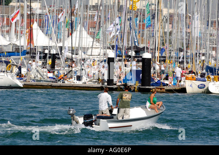 two young men and a young woman in a boat launch on the river medina at cowes during cowes week on the isle of wight - Stock Photo