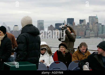 female tourist uses a point and shoot camera with cold tourists on the back of a cruise boat in new york harbour - Stock Photo