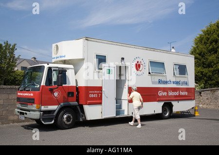 Senior woman entering mobile welsh National Blood Service vehicle parked and open for donors. UK Britain - Stock Photo