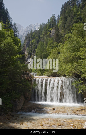 Waterfall on weir along Martuljek river with Julian Alps beyond in 'Triglav National Park'. Gozd Martuljek Slovenia - Stock Photo