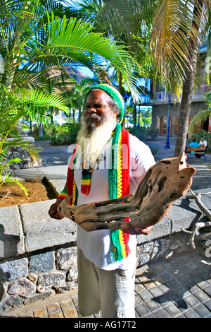 Local artist with one of his carvings - Caudan, Mauritius - Stock Photo