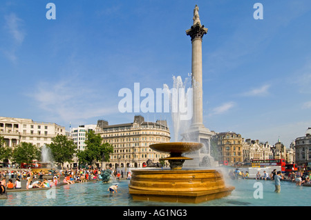 Trafalgar Square on a summers day, tourists relaxing, children playing in the water and Nelsons Column in the background. - Stock Photo