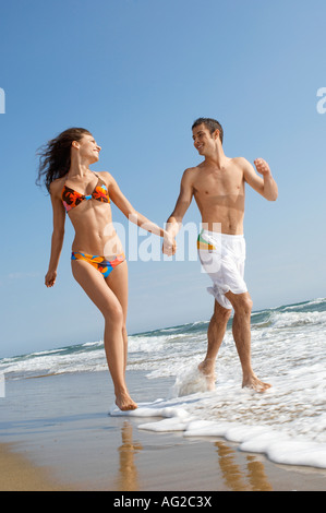 Young couple running through surf on beach, front view - Stock Photo