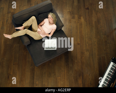 Mid adult woman sleeping on sofa, laptop beside, view from above - Stock Photo