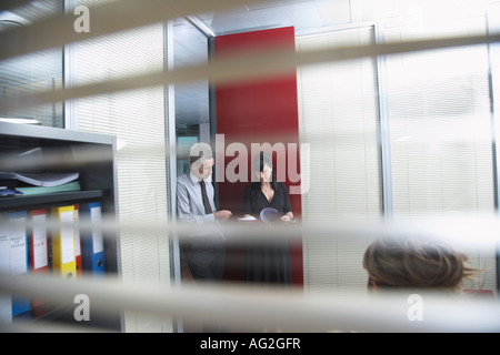 Business colleagues discussing document in office, seen through window blinds - Stock Photo