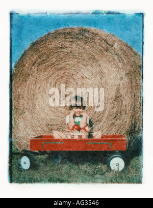 Polaroid transfer portrait of young girl in wagon in front of hay stack - Stock Photo