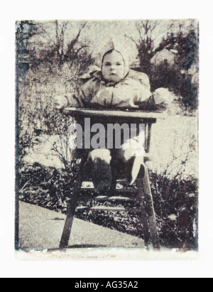 Polaroid transfer image of baby in high chair circa 1940s - Stock Photo