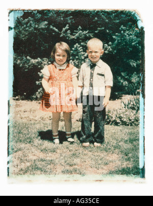Polaroid transfer portrait of siblings in front yard circa 1950s - Stock Photo
