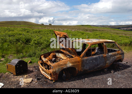 Stolen car burnt out and dumped in open countryside in South Wales UK - Stock Photo