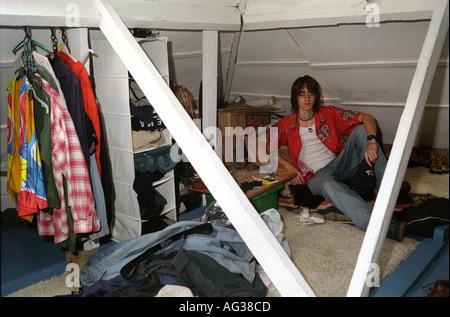 Teenaged boy in attic bedroom. - Stock Photo