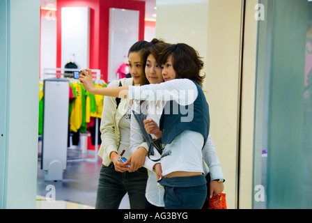 Beijing CHINA, Chinese Female Teens in Trendy CLothes taking selfies photos of themselves 'The Oriental Plaza Shopping - Stock Photo