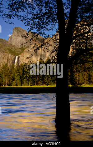 Sunset light on Bridalveil Fall over the Merced River in spring Yosemite Valley Yosemite National Park California - Stock Photo