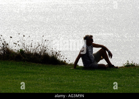 young man sitting on cliffs at sunset looking over the glistening sea watching the sun go down - Stock Photo