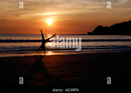 Girl cartwheeling on the beach at sunset Nicaragua - Stock Photo