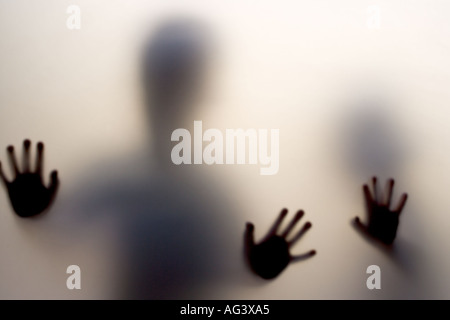 The hands of children pressed up against the frosted glass of a door - Stock Photo