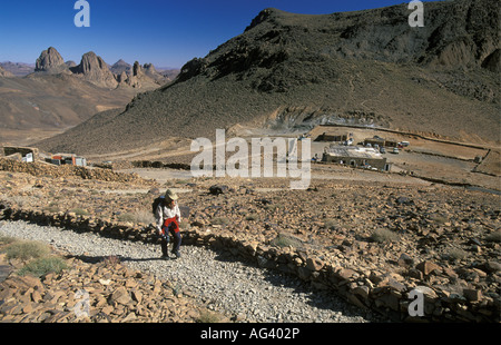 Algeria Tamanrasset Tourist hiking by Hoggar Mountains with campsite and lodge in background - Stock Photo