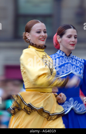 Two female dancers in yellow and blue dresses, Orenburg State Russian Folk Choir performing, Plaza Arriaga Bilbao - Stock Photo