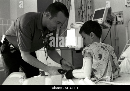 A male nurse tends to a young boy's broken arm in a children's ward of a hospital in north London, UK. - Stock Photo