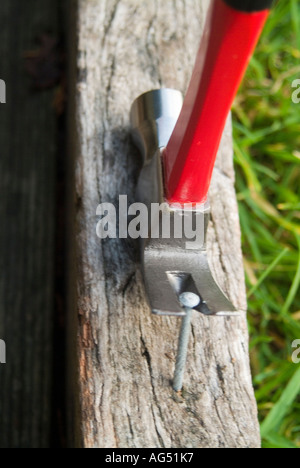 Claw hammer pulling large nail - Stock Photo
